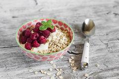 farine-d-avoine-avec-les-framboises-et-le-yaourt-naturel-dans-une-cuvette-56630681