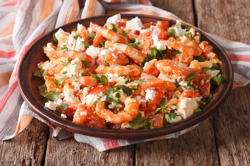 Shrimp with tomatoes and feta cheese on a plate close-up. horizontal
